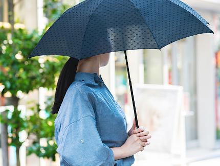 日傘で髪の紫外線対策する女性