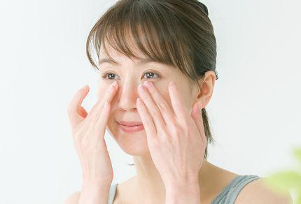 目もとをマッサージする女性
