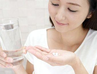 美白サプリメントを飲む女性