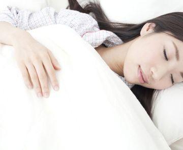 清潔な布団で眠る女性