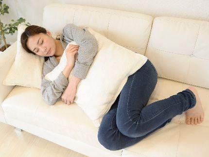 寝転んで、運動不足が気になる女性