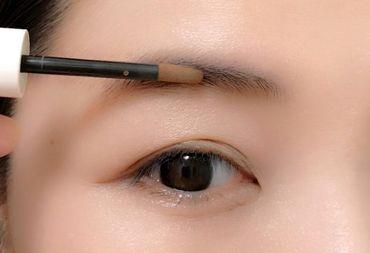 チップ型のパウダーアイブロウで眉を描く様子