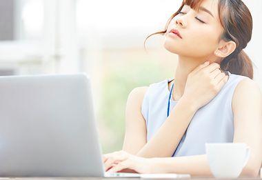 座りっぱなしのデスクワークで疲れる女性