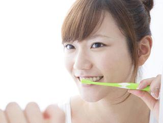 グリーンティー薬用デンタルペーストで歯磨きをする女性