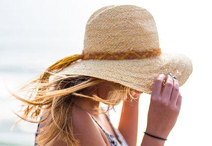 帽子をかぶって紫外線対策する女性
