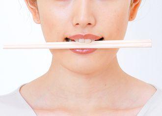 お箸を噛んでエクササイズする女性