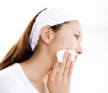 コットンで化粧水をつける女性
