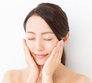 化粧水を頬につける女性