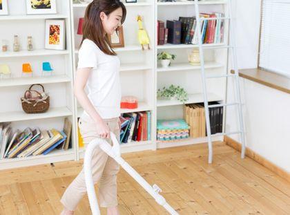 ゆったりとした服装で掃除する女性