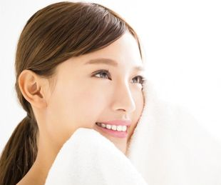 洗顔した後に顔を拭く女性