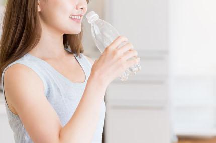 ペットボトルエクササイズでたるみを改善する女性