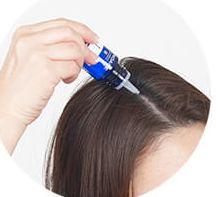 ミューノアージュWアプローチヘアの育毛剤を塗布する様子