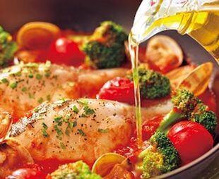 トマト料理にオリーブオイルをかける様子