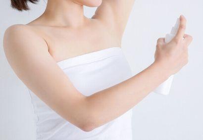 脇に制汗剤をスプレーする女性