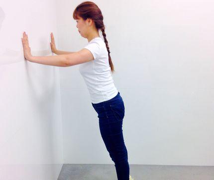 壁に手をついて腕立てをする運動