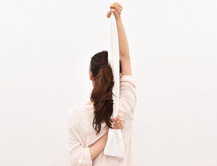 タオルを縦に引っ張って、二の腕の後ろ側を鍛える様子